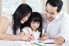 Friendly parents help their kid wrote on the book Royalty Free Stock Photos