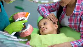 Friendly pediatric dentist explaining to child how to brush teeth properly. Stock photo stock photo
