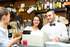 Friendly personnel working in a bar. A beautiful young waitress with a glass of wine, a bartender at a counter and administrator with a check royalty free stock images