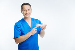 Friendly physician pointing toward pills organizer Royalty Free Stock Image