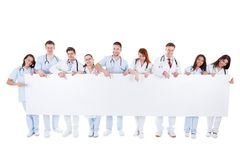 Friendly physicians holding a blank banner. A group of young and friendly physicians  wearing white coats and stethoscopes around the neck  smiling while holding Royalty Free Stock Image