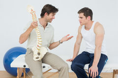 Friendly physiotherapist explaining the spine to a patient Royalty Free Stock Photography