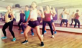 Friendly positive people learning zumba steps. In dance hall Stock Images