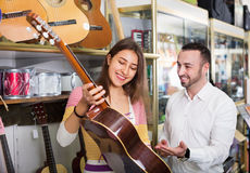 Friendly  positive shopgirl helping male client to select guitar Stock Photo