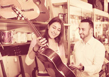 Friendly  positive shopgirl helping male client to select guitar Royalty Free Stock Photos