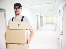 Friendly postman with parcels Royalty Free Stock Images