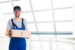 Friendly postman with parcels Royalty Free Stock Image
