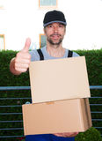 Friendly postman with parcels and thumb up Stock Image