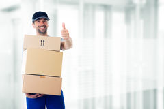 Friendly postman with parcels and thumb up Royalty Free Stock Images