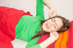 Friendly prank. Sleepy girl yawning with hand drawn mono eyebrow and moustache on her face Stock Photography