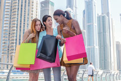 Friendly purchase. Beautiful girl in dress holding shopping bags Stock Photos
