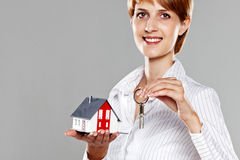 Friendly Real Estate Agent presenting a model house and keys Stock Photos