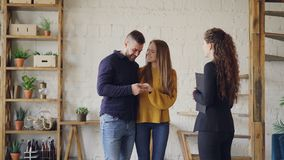Friendly realtor is giving keys to young couple buyers of new house, happy spouses are hugging and kissing, man is. Friendly realtor is giving keys to young stock video