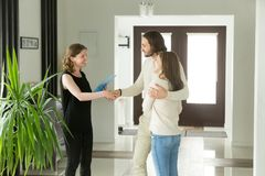 Friendly realtor and young couple shaking hands standing in hall. Way, real estate agent handshaking clients at meeting, showing selling buying property for rent Royalty Free Stock Photos