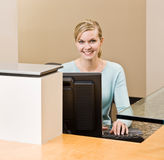 Friendly receptionist working on computer Royalty Free Stock Photography