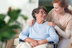 Friendly relationship between smiling nurse and happy disabled g. Randmother stock photo