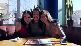Friendly relationships, girls embrace and laughing in bright dining room