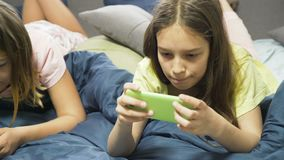 Friendly relaxed young teenage girls chatting and browsing smartphone. On bed at leisure time. modern digital device and gadgets addiction stock footage