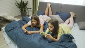 Friendly relaxed young teenage girls chatting and browsing smartphone. On bed at leisure time. modern digital device and gadgets addiction stock video footage