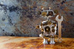 Friendly retro style steampunk robot, cogs gear wheels clock parts toy with hand wrench. Aged rusty backdrop plate. Grungy texture iron wall. Service works Stock Photos
