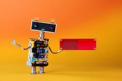Friendly robot with blank red circuit board for text. Orange yellow background, copy space stock image