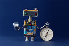 Friendly robot with magnetic exploration compass and light bulb lamp. Navigating looking for journey concept. Blue. Background. Shallow dept of field royalty free stock photography