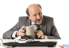 Friendly 60s bald senior business man holding coffee cup drinkin Royalty Free Stock Images