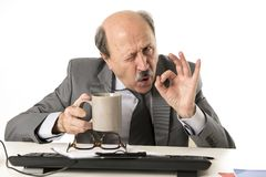 Friendly 60s bald senior business man holding coffee cup drinking happy having breakfast at office computer desk smiling. Portrait of funny and friendly 60s bald stock image