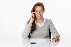 Friendly 20s business girl listening on the phone at desk Stock Photo
