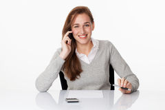 Friendly 20s business girl talking on the phone at desk Stock Photos