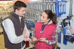 Friendly saleswoman selling to customer in hardware store. Customer royalty free stock photos