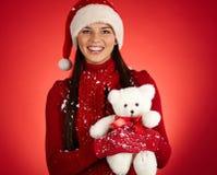 Friendly Santa. Joyful girl in Santa cap with white teddy bear posing in isolation stock images