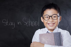 Friendly schoolboy holds book in class Stock Photo