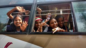 Waving children in bus. Friendly schoolgirls wave goodbye while passing tourists Royalty Free Stock Image