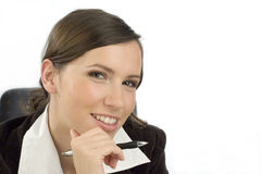Friendly secretary. Friendly looking young woman with a ball-pen in her hand Royalty Free Stock Photos