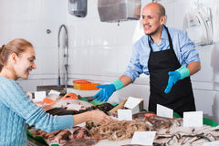 Friendly seller helping female customer to choose fish. Friendly seller helping female customer to choose chilled fish Royalty Free Stock Image