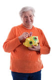Friendly senior holding a piggy bank Stock Image