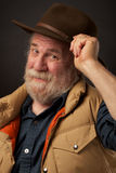 Friendly senior man tipping his hat. A friendly healthy gray bearded senior man smiles and tips his brown slouch hat with one hand. He is wearing a sleeveless Royalty Free Stock Photos