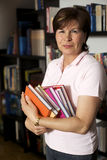 Friendly senior woman holding books Royalty Free Stock Images