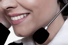 Friendly service. A close-up image of a beautiful woman with a friendly smile talking on a phone at a call centre Royalty Free Stock Photo