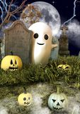A friendly sheet ghost behind a tombstone surround by Halloween pumpkins in a cemetery. royalty free stock photography