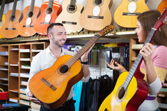 Friendly shopgirl helping male client to select guitar Stock Image