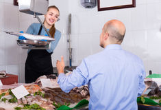 Friendly shopgirl offering fish to client Stock Photo