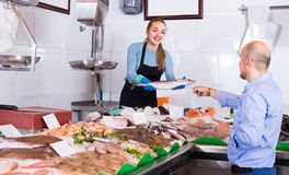 Friendly shopgirl offering fish to client Stock Image