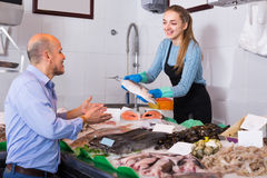 Friendly shopgirl offering fish to client Royalty Free Stock Photo