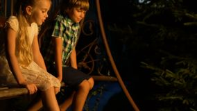 Friendly siblings enjoying cozy swing ride, spending summer holidays together stock video footage