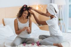 Friendly sisters preparing for party together. Always ready to help. Charming young ladies sitting on a bed and chatting while curling their hair and getting Royalty Free Stock Photo