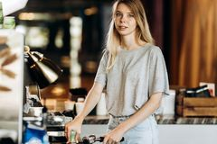 A friendly slim blonde girl,dressed in casual clothes,stands next to the coffee machine and smiles gently in a cozy royalty free stock images