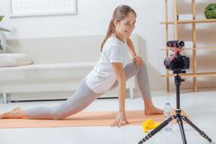 Pleasant young trainer smiling to the camera and doing her exercises stock photos