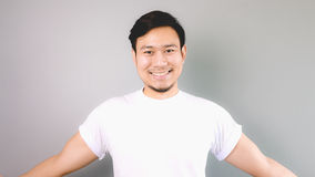 Friendly smile and ready to hug. An asian man with white t-shirt and grey background stock images